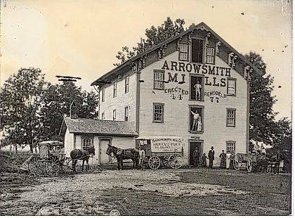 Circa 1880 photo of Arrowsmith Mills located on the east side of the Mad River just north of the southern Concord Township line in Champaign County, Ohio. A mill race diverted water from the river to the water wheel. Note the covered-like wagon with Arrowsmith Mills, Gold Lace Flour, W. H. Adlard, Urbana, Ohio written on the side. Building was erected 1844 and remodeled in 1877, as noted on the side of the building. Currently, this site is near the Birch Bark Canoe Livery on the Mad River. <em>The Champaign County Historical Society is an all-volunteer, not-for-profit organization that preserves, protects, archives and displays the artifacts that tell Champaign County&#8217;s History. The Society operates on donations and dues and has a free public museum of history at East Lawn Avenue in Urbana.</em>