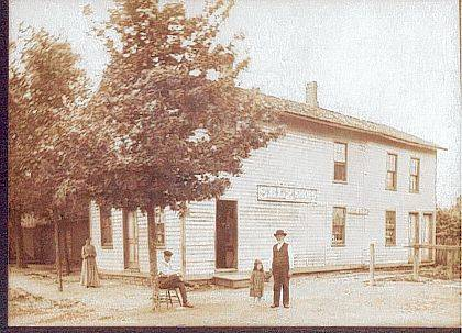 This circa 1900 photo (CCHS #A1852) is of a general store on Main Street in Cable. At one time the post office was in this building. The sign on the side of the building is an advertisement for Selz Shoes. Standing outside is a lady in a long dress. There are two gentlemen, one sitting on a chair under a tree and one standing holding a small girl&#8217;s hand. Note the wooden hitching post at the side of the building. <em>The Champaign County Historical Society is an all-volunteer, not-for-profit organization that preserves, protects, archives and displays the artifacts that tell Champaign County&#8217;s history. The society operates on donations and dues and has a free public museum of history at East Lawn Avenue in Urbana.</em>