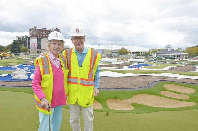 Urbana native Pete Dye and his wife, Alice, pose with the miniature golf courses they designed at the Children's Museum of Indianapolis. The holes are replicas of their most-famous designs from around the world. The attraction will open on March 17. Pete Dye is a member of the World Golf Hall of Fame.