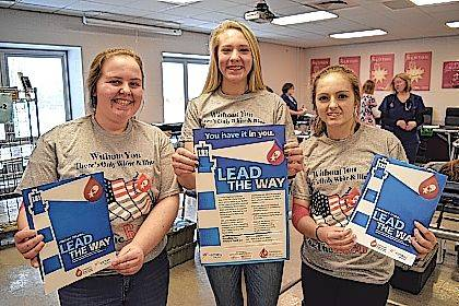 """Newton High School (Pleasant Hill) National Honor Society members Kacie Tackett, Paiton Miller and Halli Gipe wear the CBC """"Be The Red"""" high school blood drive T-shirt designed by Newton graduate Aliya Stine."""
