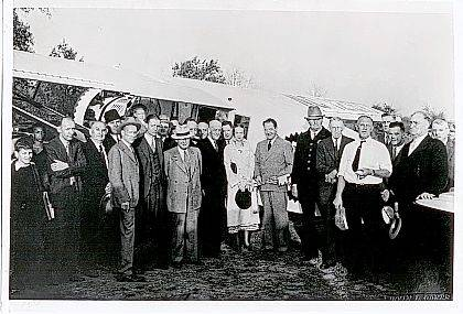 This is a photo (#0100) taken Oct. 24, 1934, of World War I Aviator Jimmy Mattern and an Urbana civic group. The group is next to the airplane Mattern flew into Urbana. He was touring under the sponsorship of the Pure Oil Co. At that time Urbana did not yet have an airport, so he landed in a pasture south of Urbana. County Prosecutor Grace Fern Heck represented county government. She was the first woman in the state to serve as prosecuting attorney. Also she was Ohio&#8217;s first female municipal court judge. On her right is W.W. Rock, mayor of Urbana, and on her left is Mattern. Also in the photo is Warren Grimes (3rd from the left). Perhaps this event prompted him to consider establishing an airport in Urbana. <em>The Champaign County Historical Society is an all-volunteer, not-for-profit organization that preserves, protects, archives and displays the artifacts that tell Champaign County&#8217;s History. The Society operates on donations and dues and has a free public museum of history at East Lawn Avenue in Urbana.</em>