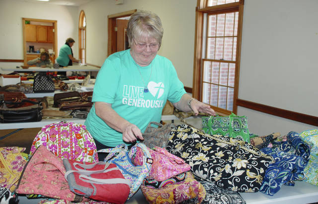 Village of St. Paris Mayor Brenda Cook arranges a table of colorfully patterned bags and purses in preparation for the Old Bag Sale on Sunday at the Evans-Purk Fellowship Hall. The fund-raiser held its 13th annual event to support the American Cancer Society's Relay for Life - which is scheduled for Friday, May 18 at the Champaign County Fairgrounds. Leading up to Sunday's event, the Old Bag Sale had raised $30,000 over 12 years.