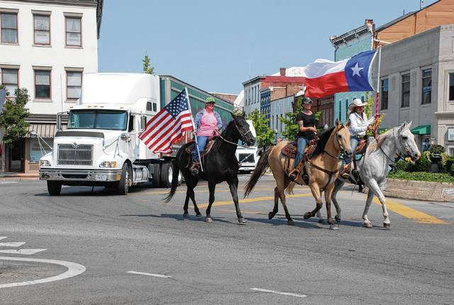Urbana Daily Citizen file photo Riders on horseback displaying the American flag and the Texas flag lead a convoy of four semi-trucks loaded with hay and other relief items through Monument Square on Sunday, Sept. 10, 2017. The convoy was headed to the Houston, Texas area to assist in the aftermath of Hurricane Harvey. When Harvey struck coastal Texas, Champaign Countians did not expect to be hauling hay to Texas. But that's what happened.