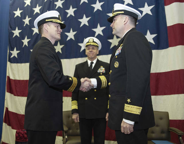"Adm. Phil Davidson (center), Commander, U.S. Fleet Forces, observes as Rear Adm. Jeff Hughes (left) and Rear Adm. John B. ""Brad"" Skillman shake hands during a change of command ceremony in Norfolk, Virginia on March 9 in which Skillman relieved Hughes as Commander, Expeditionary Strike Group 2, in the hangar bay of the amphibious assault ship USS Kearsarge (LHD 3)."