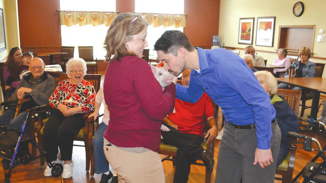 Urbana Place's area sales specialist Zach Liggett kisses a pig Monday as his reward for raising the most money in his piggy bank for the facility's fundraiser for muscular dystrophy research on Monday. Urbana Place raised $104. Life Enrichment Coordinator Shayla Smith holds the pig borrowed from Rynoka Farms. IH Credit Union donated the piggy banks.