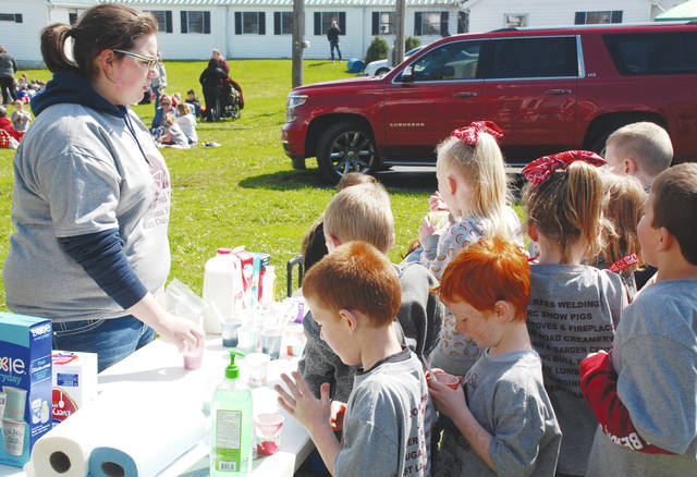Urbana FFA member McKinley Preece (left) hands out milk samples to Urbana first-graders on Thursday at Dugan Road Creamery. The students toured the facility during a visit coordinated by the Urbana FFA.