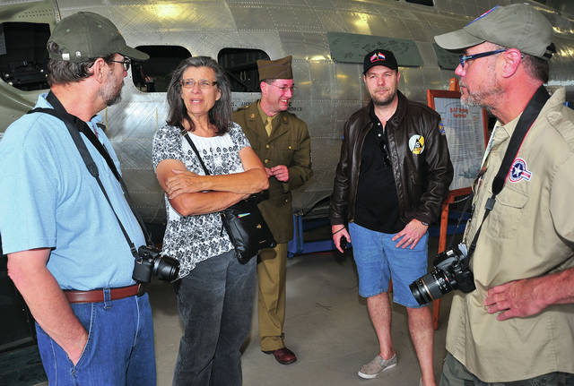 Mike Ullery | AIM Media Midwest Dan and, Janice Dana Ehrlich, along with Paul Bellamy, Andy Swinnen, and Greg Schafer, l-r, chat in front of B-17 <em>Champaign Lady</em> at Grimes Air Field on Monday during the first day of The Gather of B-17s event in Urbana. The Dana&#8217;s father was a waist gunner in a B-17 during World War II. Bellamy, who is from England and Swinnen, who traveled from the Netherlands for the event, are both historians on the 401st Bomb Group, of which Champaign Lady was a part. Schafer is a volunteer for the Champaign Aviation Museum. The events of today lead up to the a reunion of the 401st Bomb Group later this week and the debut of the newly-restored B-17 <em>Memphis Belle</em> at the National Museum of the United States Air Force on Thursday.