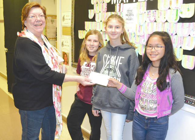 From left, Eileen James, patient service director of the Cancer Association of Champaign County, left, accepts a check for $60 from sixth graders Logan Dale, Mia Langis and Mikala McClung at Urbana Local School on April 27. The students sold glass stones and drawings door to door in the Pullins Woods subdivision the previous weekend. Logan Dale is growing his hair out to contribute to making wigs for chemotherapy patients.