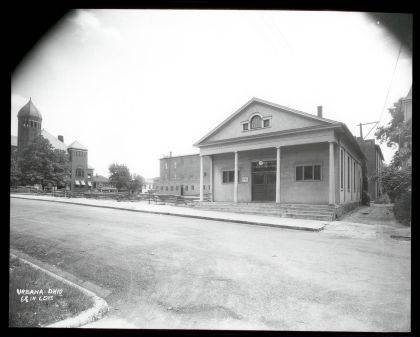 Then - Library A circa 1932 photo (CCHS #0028 & #0029) of Urbana Public Library located on the south side of West Market St. in Urbana. Currently this is the site of the U.S. Post Office alley parking lot. Note 'Clifford Theater' and old City Building (far left) are in the background. Also note the construction site of the post office building east of the library. In 1932 the Urbana Library Association acquired the building across the street at 160 W. Market St. (at the NE corner of W. Market & Walnut streets) and moved the library there. In 1996 the library moved to a remodeled building at 1060 Scioto St. (its current location). (Historical Facts and Trivia of Champaign County, Ohio by Ed Ridder)
