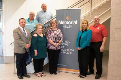 Pictured at the check presentations were, front from left, Scott DeLong, Champaign Residential Services Inc.; Marilyn Cohn, Caring Kitchen Inc.; Robin Coffey, Memorial Health Communications & Public Relations; Staci Weller, GrandWorks Foundation; Paul Waldsmith, Champaign Family YMCA; back from left, Don Richardson, PAWS Animal Shelter; and Brett Evilsizor, Cancer Association of Champaign County.