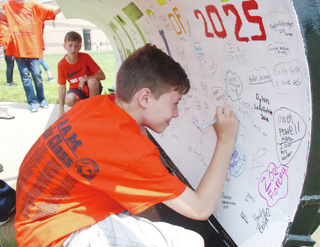 Fifth-grader Matthew Lucier signs his name to a snow plow during the last day of school at Graham Elementary on Thursday. Awards and activities among the students were part of the big day before summer break begins.