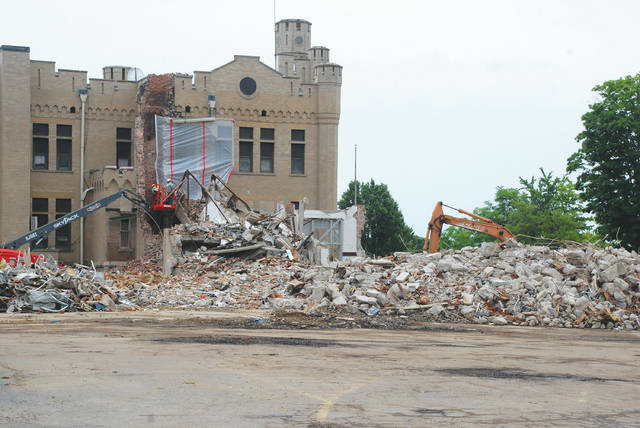 As progress continues on the new Urbana High School site, crews are pictured on Friday at The Castle building. Part of the buildings around The Castle required demolition and this picture shows a rear turret to the northeast side has fallen down. Plans are to retain The Castle and use it for something other than classrooms. According to Urbana City School Superintendent Charles Thiel, unexpected damage occurred on Wednesday while the old connecting overpass walkway was being prepared for demolition between The Castle and the old Junior High. As workers removed the brick and roof from the outside involving the overpass walkway, a piece of the walkway fell and slipped into an anchor spot on the Junior High building, twisted and hit the brick on the turret - causing the turret to crumble shortly thereafter. A structural engineer reviewed the area on Friday and it does not appear there is structural damage to The Castle itself, Thiel said. The plan is to shore up the area and then remove the rest of the overpass walkway. Workers will retrieve the old bricks that fell, which are specially cut, to replace and repair the turret. The damage is believed to be covered by an insurance company involved with the project, Thiel said.
