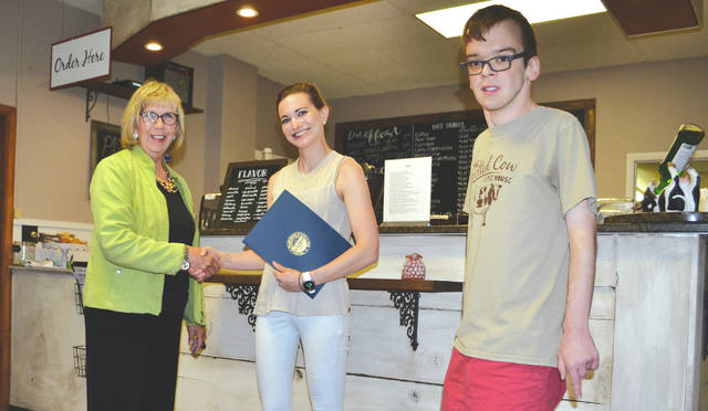 Regional Liaison for the Ohio Secretary of State Elaine Herrick presents a commendation to Bobbi Custer, owner of the Spotted Cow Coffeehouse, for her efforts to employ workers who have developmental disabilities such as Burr Simpson (right). Spotted Cow has been in operation since May 2014 and works closely with Downsize Farms to provide opportunities to developmentally disabled individuals in Champaign County.