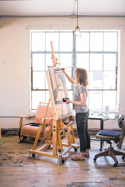 The featured artist of this year's Art Affair on the Square is Kelley Booze, shown here working in her studio.