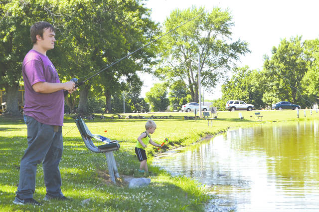 Stephen Talbot-Woltz and his son, 2-year-old Lucas, enjoy fishing in the pond at Melvin Miller Park on Monday.