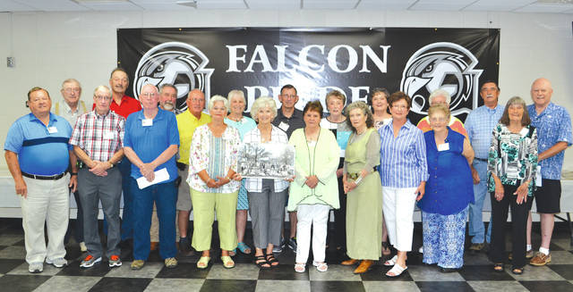 Members of the first graduating class from Graham High School in 1958 hold up a photo taken in April of that year, before eating lunch at their reunion in the Graham High School cafeteria on Friday, July 13. Organizers said there were 58 members of the original graduating class and 21 classmates at this reunion. Classmates began meeting annually after the 50th anniversary reunion, but typically meet at St. Paris Lutheran Church. Many members of the 1958 class said they were looking forward to a tour of the school building during the reunion.