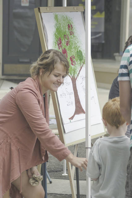 At the Johnny Appleseed Museum tent during Art Affair, the activity was painting. Pictured is Kasey Shaw with young visitor. The annual event was held in downtown Urbana on Saturday despite cool, rainy conditions.