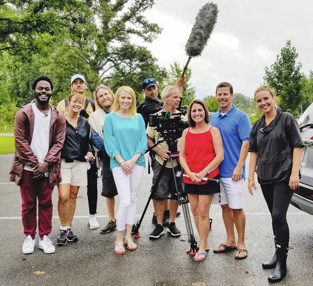 """Local Realtor Paige Duff (at left of camera) poses with the production crew from Left Right LLC of New York City and two of the the local homebuyers to be featured on the show. They just wrapped up shooting two new episodes to air later this year on HGTV's """"Island Life"""" reality show."""
