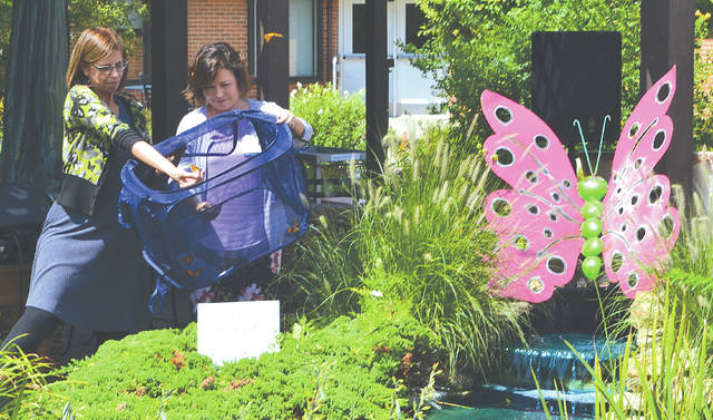 Tonya West, director of resident services at Mercy Health McAuley Senior Living Center, and Jessica Pettit, director of volunteer and auxiliary services at Mercy Health Urbana Hospital, release 12 Monarch butterflies into the courtyard of the Senior Living Center on Wednesday.