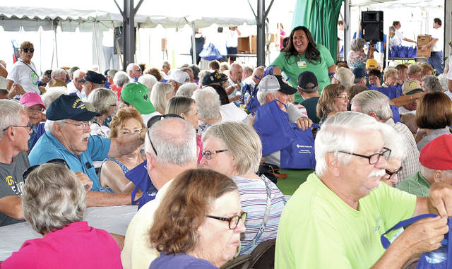Annette Turner, executive director of Mercy Health-Oakwood Village, Springfield, helps distribute more than 1,400 lunches to senior citizens and veterans at the Champaign County Fair on Tuesday.