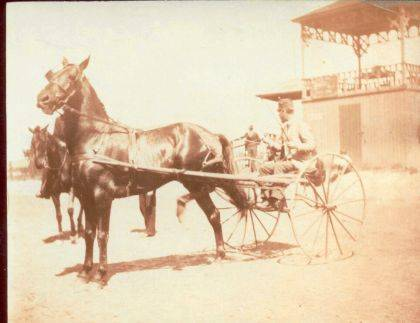 Then - Aug. 28, 1891, at the Champaign County Fair with harness horse hitched to high-wheeled racing sulky on the racetrack in front of the judges' stand (CCHS #A1745). In 1892 this high-wheeled racing sulky was superseded by bicycle pneumatic tired-sulky, a modification still used today. Note the elaborate judges' stand. July 4, 1911 photo (CCHS #A1704) shows this judges' stand in front of the grandstand. It is not known when this judges' stand was replaced.