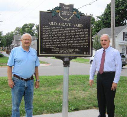 """Dan Walter, left, president of the Champaign County Historical Society, and Kerry Brugger, city Director of Administration, stand by the re-installed Ohio Historical Marker at Urbana's first graveyard. In 2014 the historical society, the city and others dedicated the marker at the northeast corner of Kenton and Ward streets to commemorate the graveyard (1805-1855) and the War Council of 1812, which took place about 100 yards to the west. Last year the marker suffered significant damage and was returned to the manufacturer for repair. """"We sincerely appreciate Director Brugger and the city of Urbana taking the initiative to repair and re-install this important marker,"""" said Walter. """"People need to understand that considerable research and monies go into the creation of Ohio Historical Markers and that they need to be protected."""""""