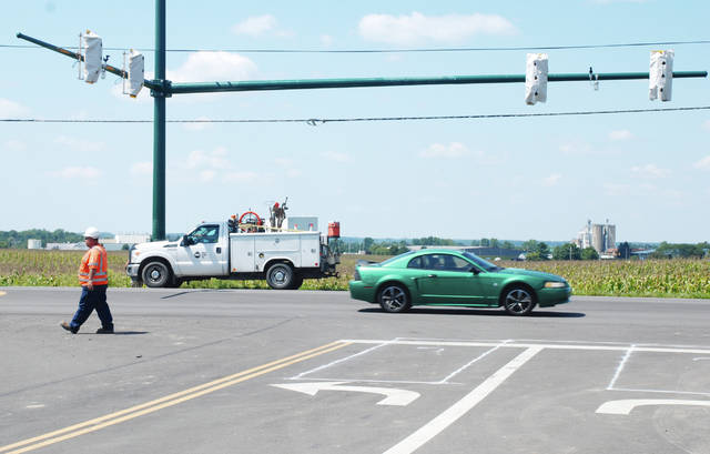 Newly-installed traffic signal lights are shown at the U.S. Route 68 entrance/exit of the new Urbana pre-K through eighth-grade elementary school this week. In photo, contractors finish the installation of the signal lights, which remain wrapped in protective plastic leading up to their implementation when the new school opens September 11.